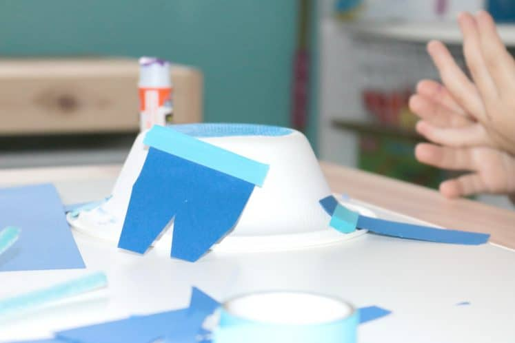 preschooler taping fins to whale craft