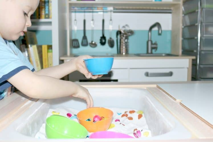 child putting colorful gems in small bowl