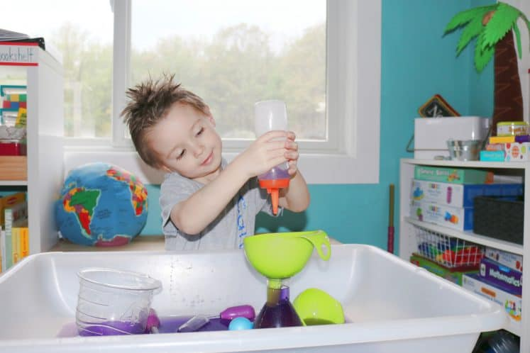 child squirting colored water into funnel