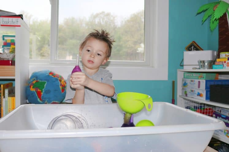 preschooler squirting water in eyedropper upward