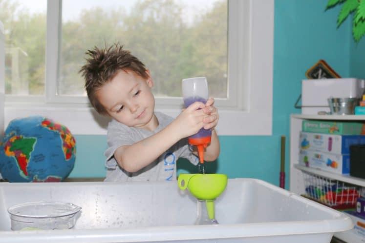 preschooler squirting purple water into funnel