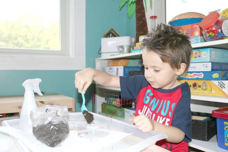 preschooler scooping dirt into plastic container
