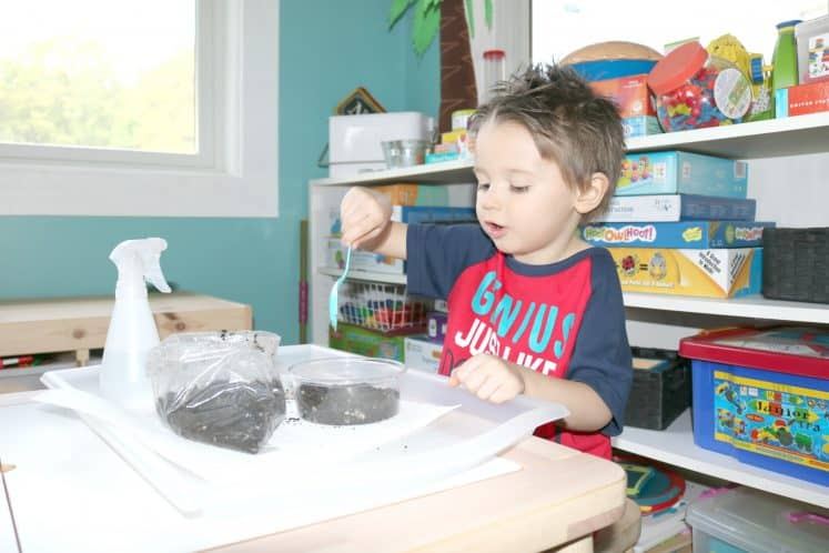 preschooler scooping dirt into plastic container to plant grass
