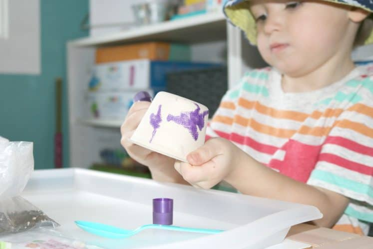 preschooler painting small cup