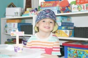preschooler smiling with gardening craft