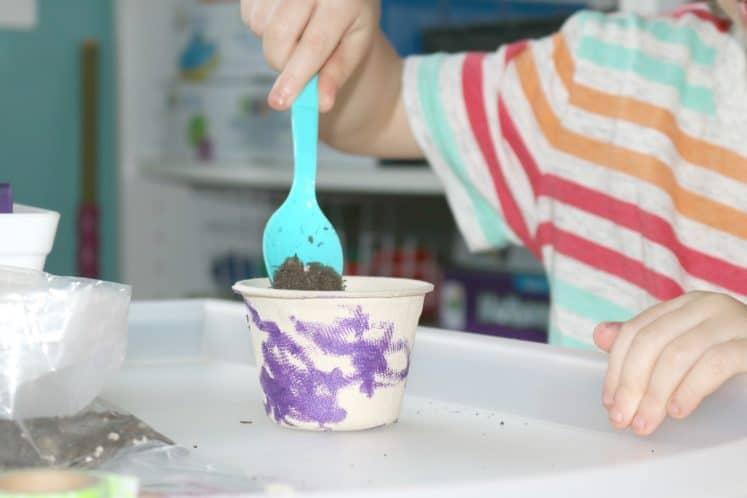 preschooler scooping dirt into small cup