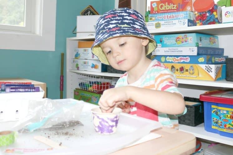 preschooler placing seed into small cup
