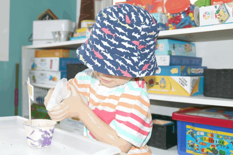 preschooler spraying seed with water