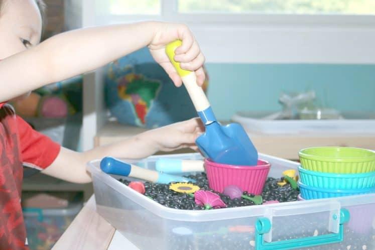 preschooler scooping pretend dirt into flower pot