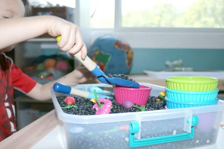 preschooler digging in gardening sensory bin