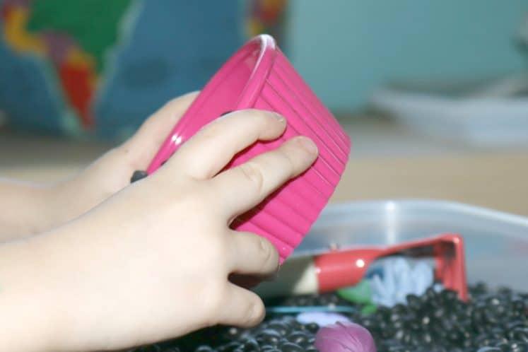 preschooler dumping small dish of pretend dirt into gardening sensory bin