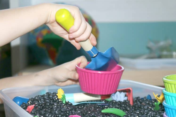 preschooler scooping pretend dirt into gardening sensory bin