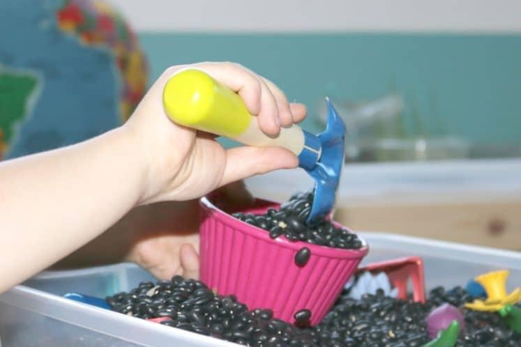 preschooler filling flower pot with pretend dirt