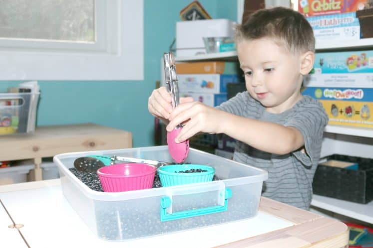 preschooler exploring tongs in sensory bin