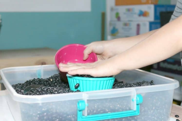 preschooler filling one small bowl using another