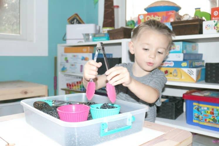 preschooler using tongs to move material in sensory bin