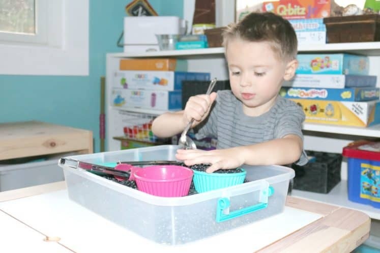 preschooler using spoon to move material in sensory bin