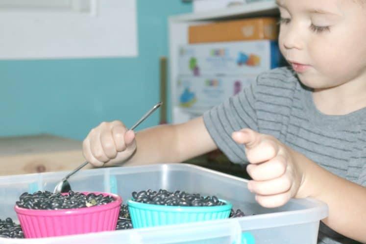 preschooler scooping material from sensory bin