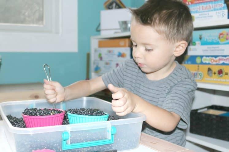 preschooler scooping material in kitchen utensil sensory bin
