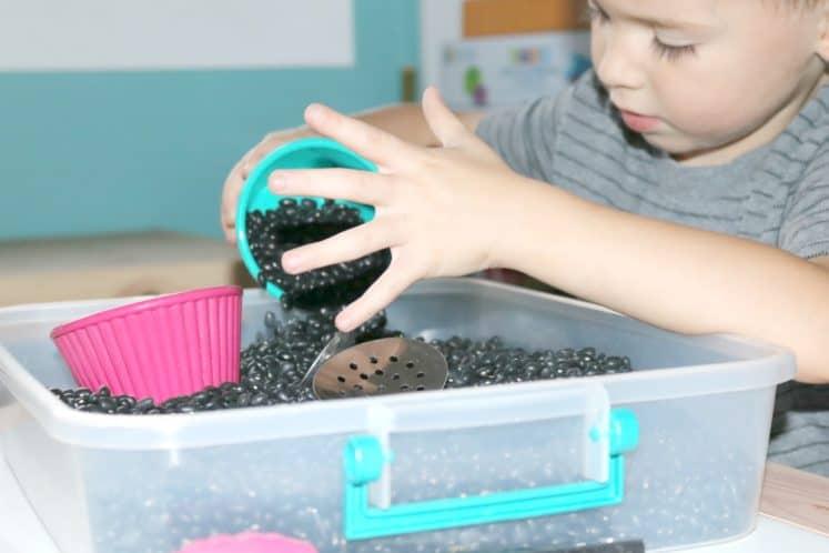 preschooler pouring beans into sensory bin