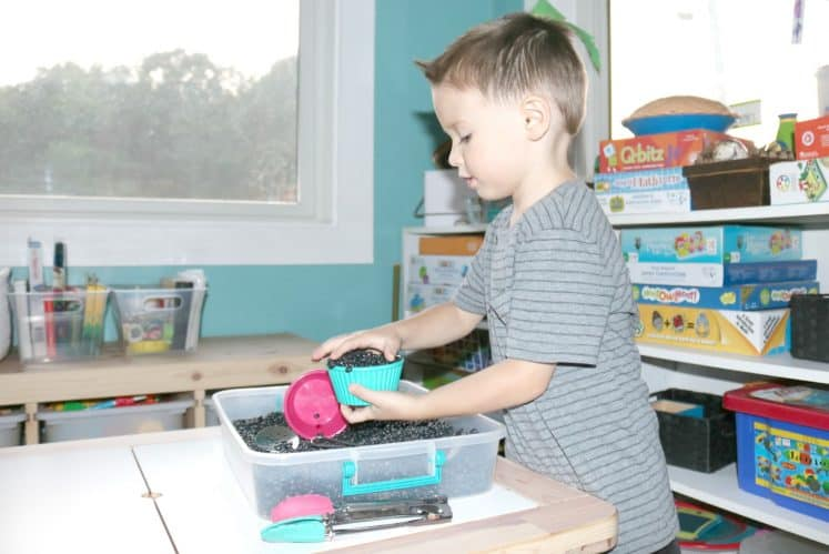 preschooler filling small bowl from sensory bin