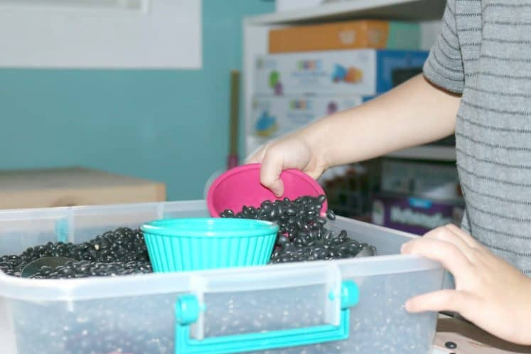 preschooler using small bowl to scoop material from sensory bin