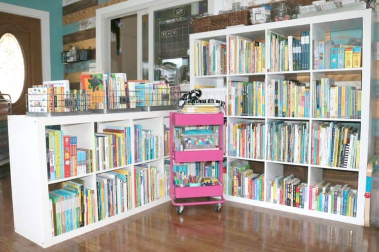 rolling cart in front of perpendicular cube bookshelves filled with children's books