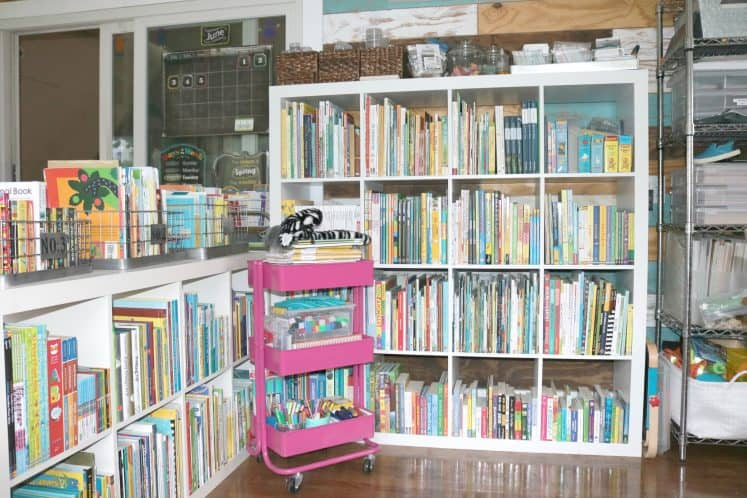 homeschool library featuring rolling cart filled with supplies in front of two cube bookshelves