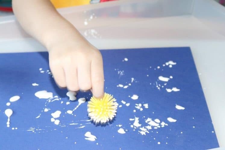 preschooler dabbing pokey ball on cardstock to make flower craft
