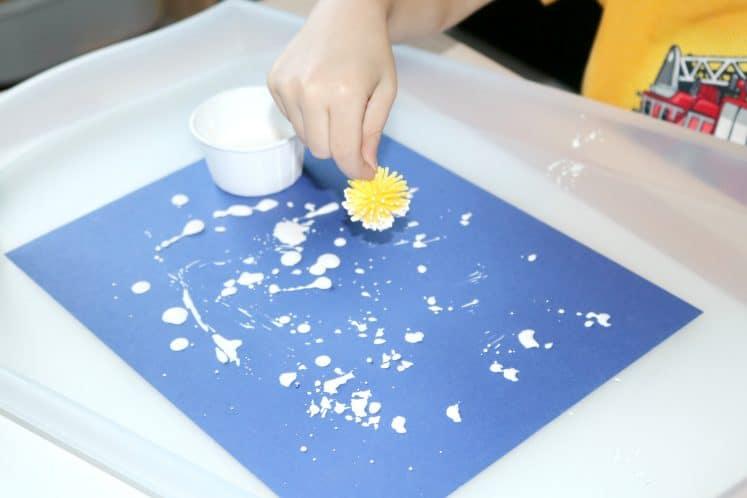 preschooler using pokey ball to paint dandelion art on blue cardstock