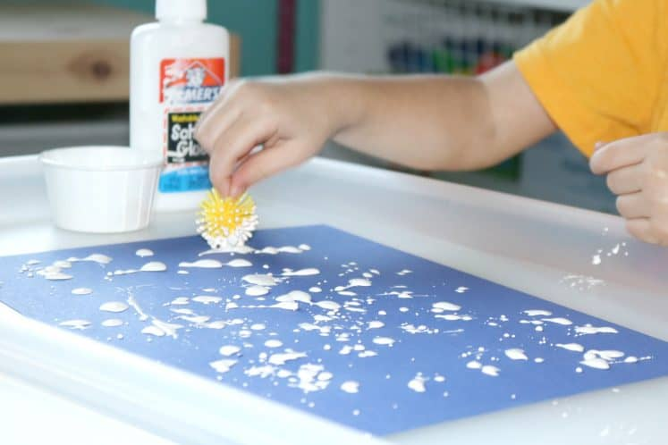 preschooler painting flowers with pokey ball