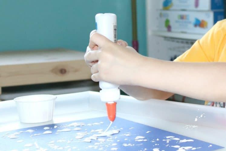 preschooler squeezing glue onto cardstock