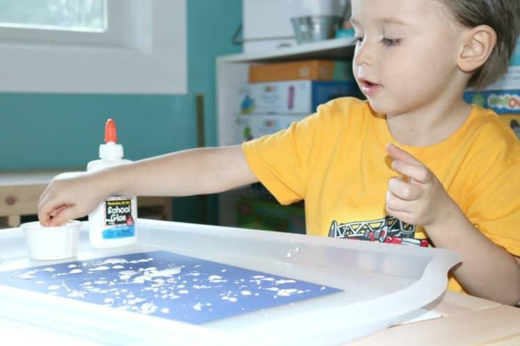 preschooler dipping pokey ball in paint