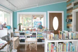 preschool homeschool space with small table and shelves filled with books and toys