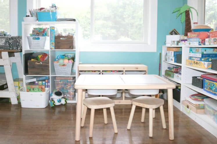 preschool homeschool space with sensory table and shelves filled with books and toys