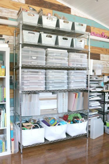 wire shelf filled with scrapbooking supplies organized into a variety of baskets and containers