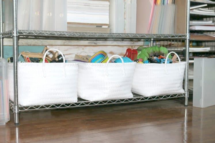 children's toys in three wicker baskets on bottom shelf of wire storage rack