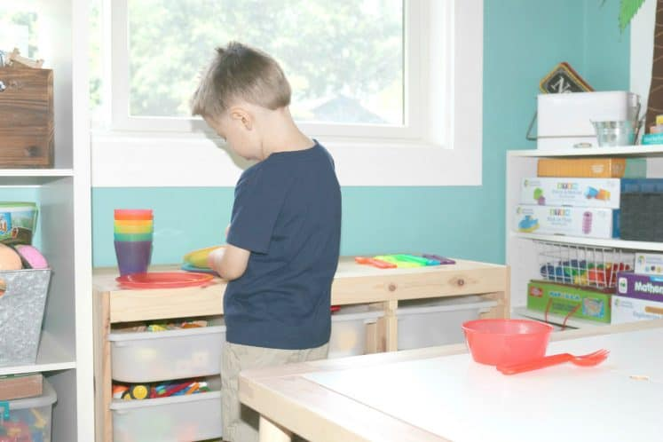 preschooler setting pretend table for dramatic play activity