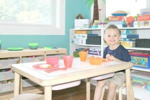 preschooler sitting at table set for mealtime