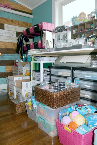 variety of baskets and bins containing supplies on the floor in front of craft workspace