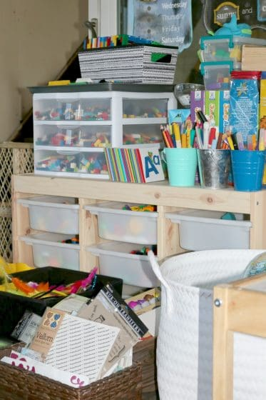 baskets of craft supplies in front of shelf with kids science and building supplies, art materials and manipulatives