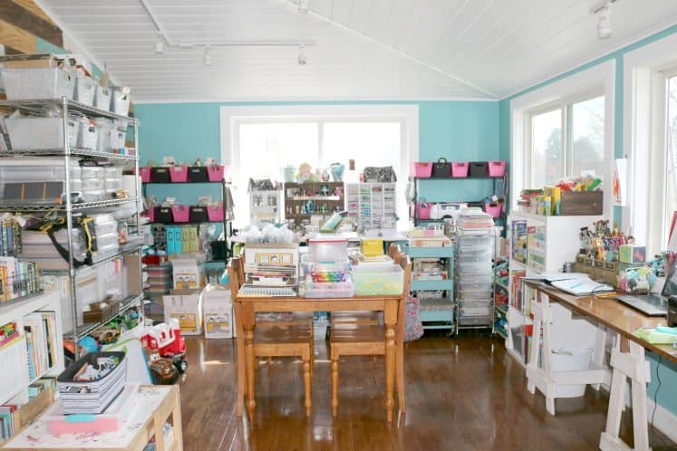 craft room with wooden table and chairs and several shelves filled with supplies