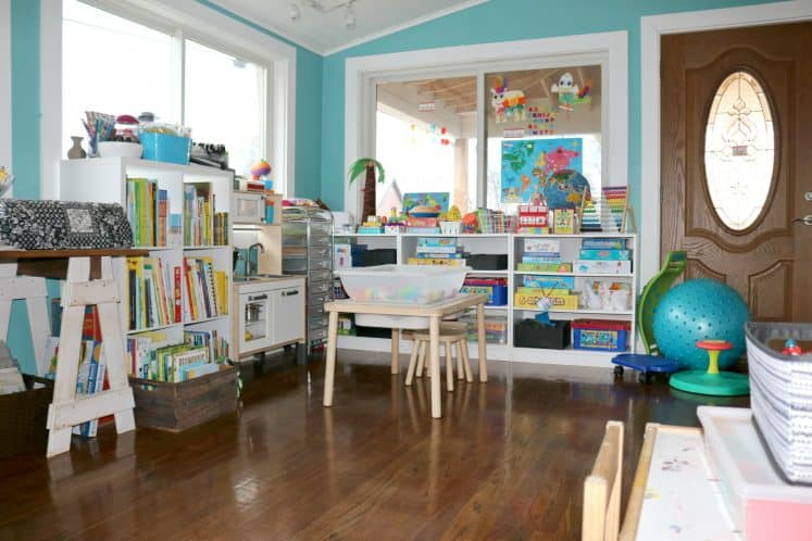 kids play area featuring pretend kitchen, sensory table with stools, and bookcases filled with puzzles and games