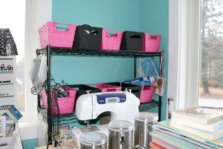 wire shelves containing baskets of mixed media and art journaling supplies