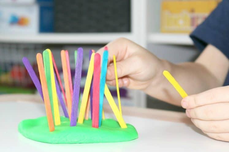 preschooler pulling craft sticks from green play dough