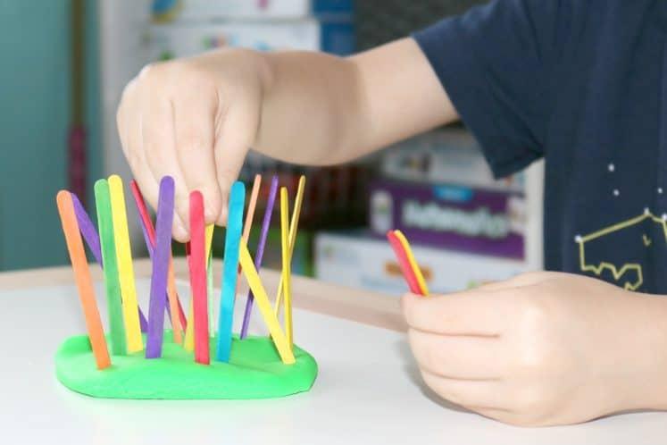 preschooler pushing craft sticks into play dough