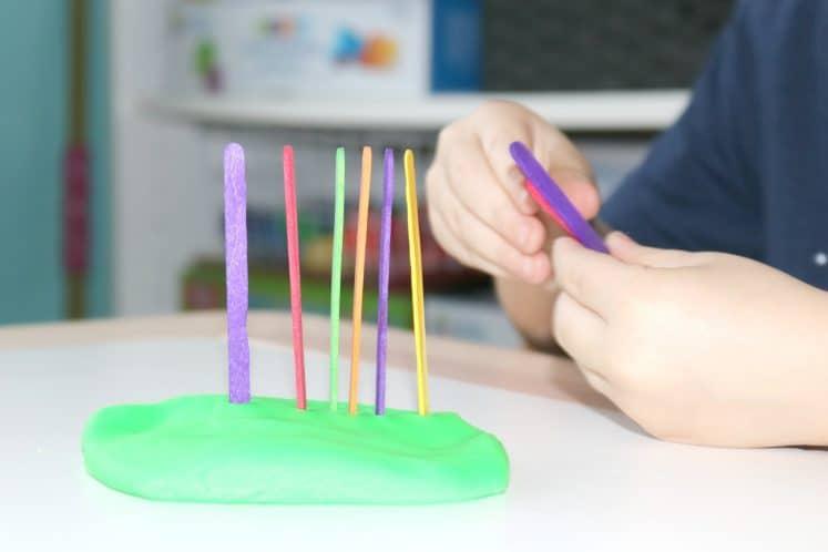 preschooler removing craft sticks from play dough