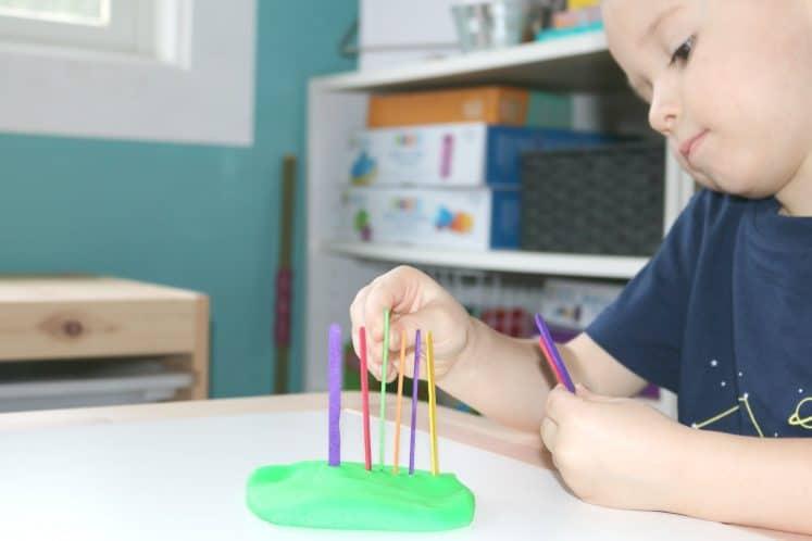 preschooler counting craft sticks in play dough garden