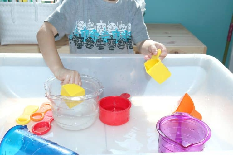 preschooler practicing estimation skills with measuring cups and water