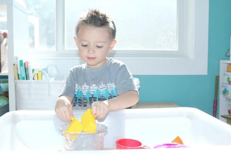 preschooler exploring estimation activity using measuring cups and water
